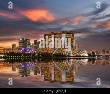 Sunset over the Singapore skyline, with Marina Bay Sands and the Gardens on the Bay reflecting in Marina Bay. - Stock Photo