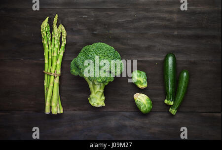 Fresh green organic vegetables on black wooden vintage table.Top view - Stock Photo