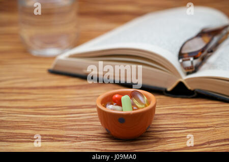 An old hardbound book, pair of broken reader glasses on it, a bunch of pills in a container, on wooden table, suggesting - Stock Photo