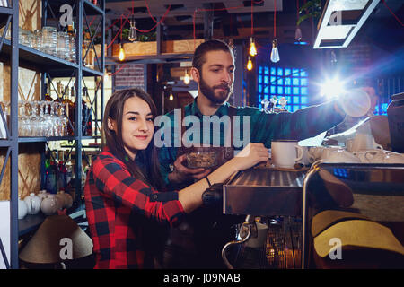 Girl waiter the barman works behind a bar rack in cafe restaurant - Stock Photo