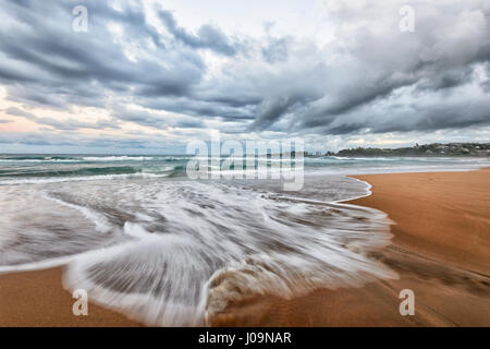 Dramatic view of an impending storm and waves motion blur at Bombo Beach, Kiama, Illawarra Coast, New South Wales, - Stock Photo