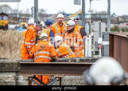 Rail construction workers installing a girder bridge - Stock Photo