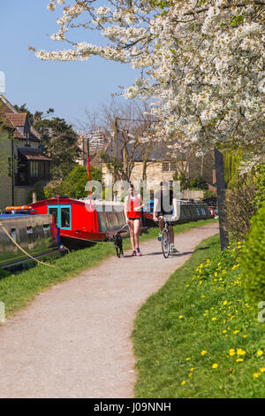 Young man riding bike with young woman walking dog along pathway by Kennet & Avon canal at Bradford on Avon, Wiltshire - Stock Photo