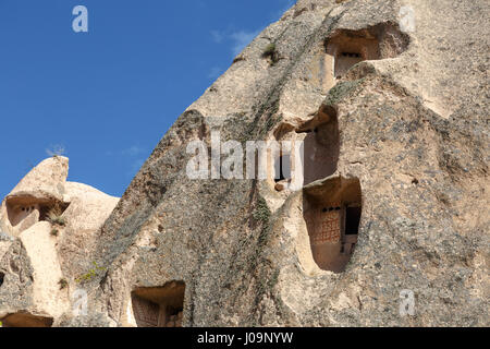 Close up detailed view of small sandstone tufa caves, on bright blue sky background. - Stock Photo