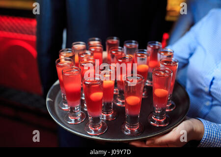 Glasses with red cocktails on a tray in the hands of the waiter. Side view - Stock Photo