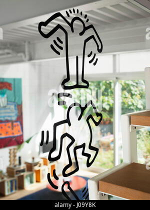 Keith Haring sticker on the glass screen between staircase and living room. 174 Grand Street, New York, United States. - Stock Photo