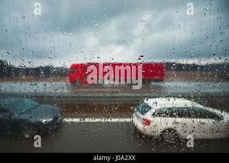 Close up view on the raindrops. Traffic on the highway in the rain. - Stock Photo