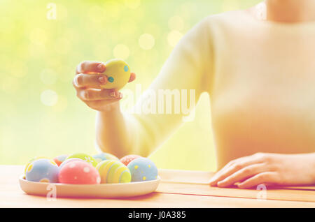 close up of woman hands with colored easter eggs - Stock Photo