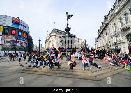 PICCADILLY CIRCUS London – June 06, 2014: People enjoying the sun at Piccadilly Circus London - Stock Photo