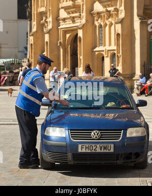Parking enforcement officer giving out a ticket. - Stock Photo