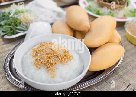 Close focus on sticky rice covered by roasted soybeans in white bowl with yellow mango on plate. - Stock Photo