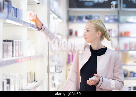 Beautiful woman shopping in beauty store. - Stock Photo