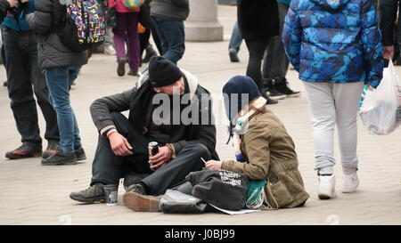 two people sitting on a cold London street drinking and talking in front of man playing guitar - Stock Photo