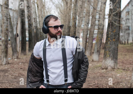 man with beard and headphones in the park - Stock Photo