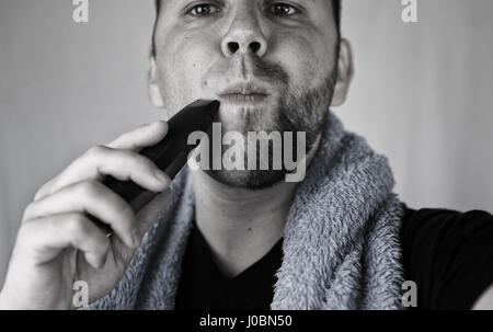 monochrome textured portrait bearded man shaving - Stock Photo