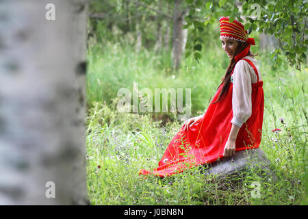 Slav in traditional dress is sitting in nature - Stock Photo