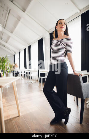 Portrait of beautiful young woman standing in a cafe leaning on chair and looking away smiling. Successful female - Stock Photo