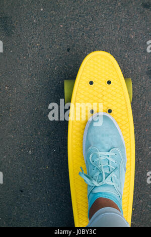 Women's leg in blue jeans and sneakers standing on yellow skateboard, point of view, vertical framing - Stock Photo