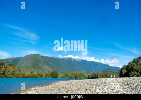 Fishermen walking along a shingle beach next to the trout-filled Puelo River in Northern Patagonia, Chile - Stock Photo