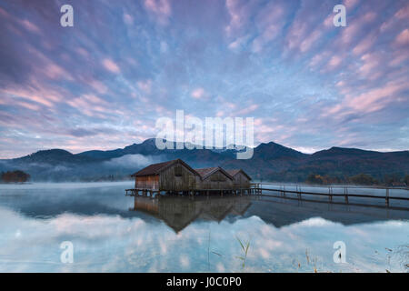 Pink clouds at sunset and wooden huts are reflected in the clear water of Kochelsee, Schlehdorf, Bavaria, Germany - Stock Photo