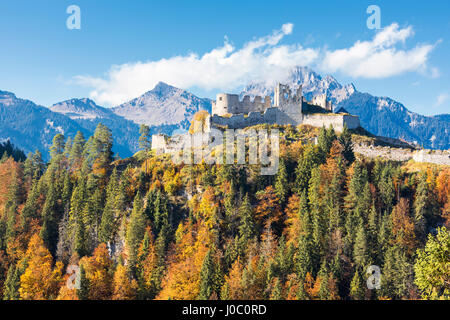 View of the old Ehrenberg Castle surrounded by colorful woods and rocky peaks, Reutte, Austria - Stock Photo