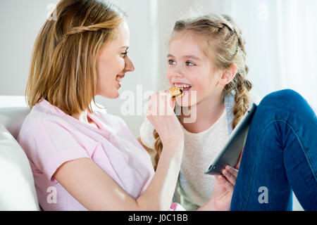 Happy mother feeding daughter with cookie while using digital tablet - Stock Photo