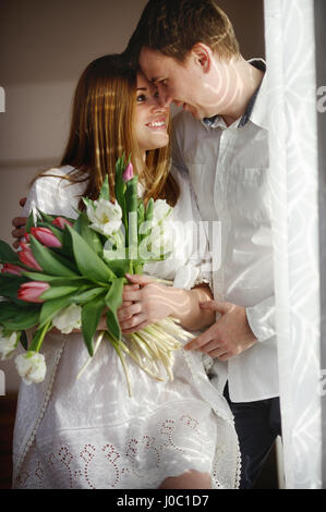 Young man congratulates his woman. She sits in a beautiful white dress with a bouquet of multi-coloured tulips. - Stock Photo