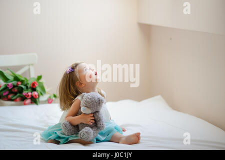 The charming little girl sits barefoot on a big bed. In hands at the baby a gray teddy bear. The girl with curiosity - Stock Photo