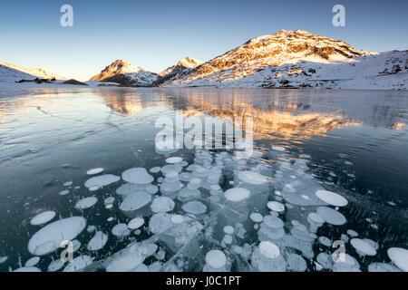 Ice bubbles at sunrise, Bianco Lake, Bernina Pass, Engadine, Switzerland - Stock Photo