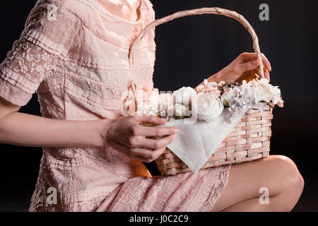 Cropped shot of young woman in pink dress holding flower basket - Stock Photo
