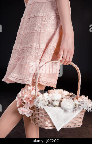 Cropped shot of young woman in pink dress walking with flower basket - Stock Photo