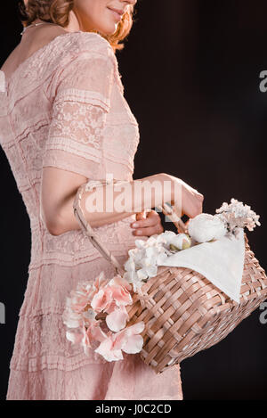 Cropped shot of young woman in pink dress holding flower basket on black - Stock Photo