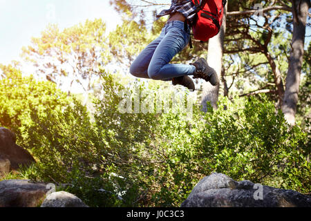 Young woman, wearing backpack, jumping in air, low section - Stock Photo