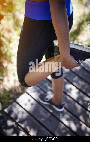 Young woman outdoors, exercising, stretching, low section - Stock Photo