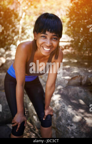 Portrait of young woman outdoors, hands on knees, smiling - Stock Photo
