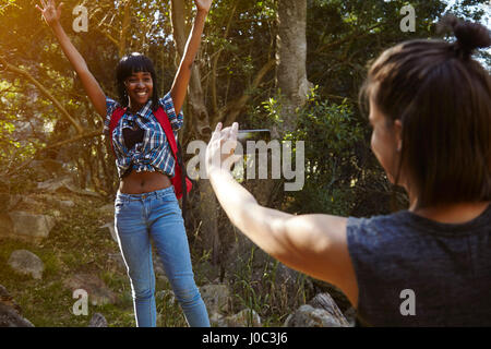 Two friends hiking, young woman taking photograph of friend, using smartphone, Cape Town, South Africa - Stock Photo