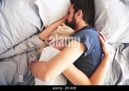 Couple lying in bed together, sleeping, arms around each other - Stock Photo