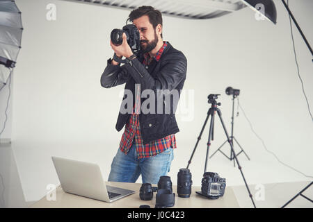 Male photographer testing digital SLR focus for studio photo - Stock Photo