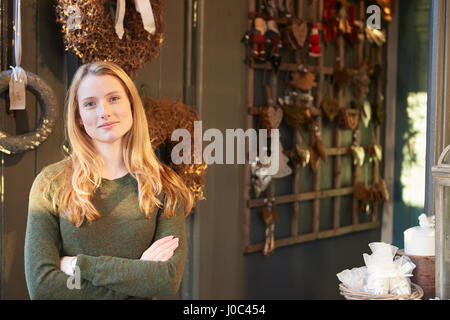 Portrait of young woman standing in shop doorway, arms folded - Stock Photo