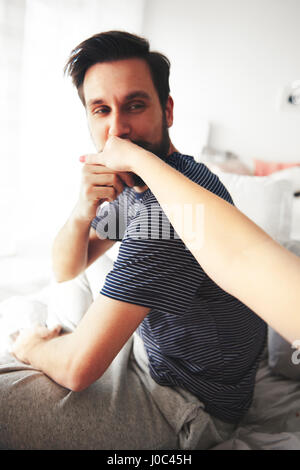 Man sitting on bed, kissing woman's hand - Stock Photo