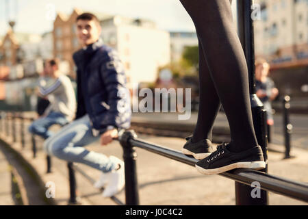 Young man sitting on railing, young girl walking along railing next to him, Bristol, UK - Stock Photo