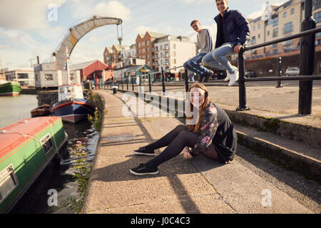 Portrait of three friends sitting beside river, Bristol, UK - Stock Photo