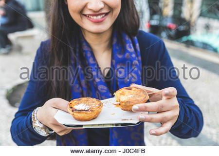 Woman holding pastel de nata, Lisbon, Portugal - Stock Photo