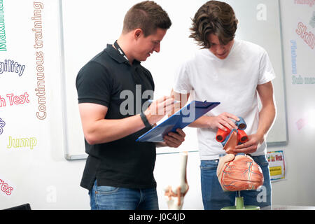 Male student holding model heart valves, being assessed by tutor in biology class - Stock Photo