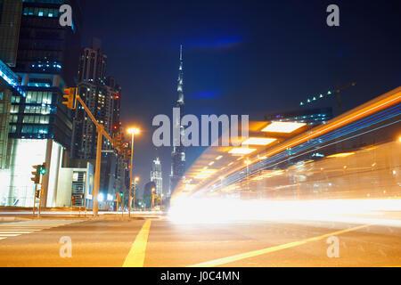 Cityscape at night showing Burj Khalifa in background and light trails, Dubai, UAE - Stock Photo