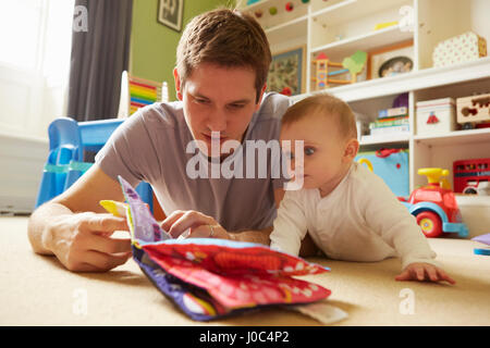 Mid adult man and baby daughter reading storybook in playroom - Stock Photo