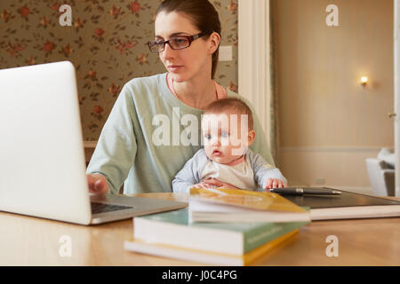 Baby girl sitting on mother's lap staring at laptop - Stock Photo