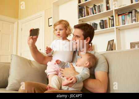 Mid adult man taking smartphone selfie with toddler and baby daughter on sofa - Stock Photo