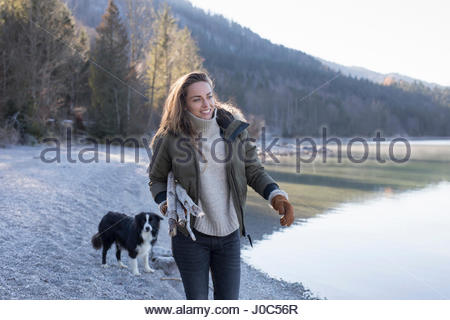 Woman walking dog on lakeside in Bavarian Alps - Stock Photo