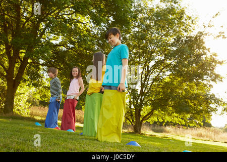 Girls and boys on start line for sack race in park - Stock Photo